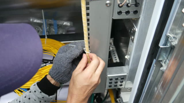 Technical worker is doing rearrange fiber optic cable in telecomunication equipment rack