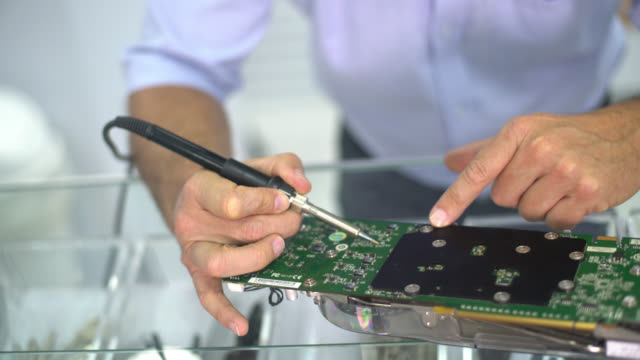 IT technician fixing a motherboard video
