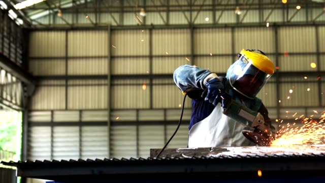 Technician grinding metal With an electric grinder in a uniform and wearing safety equipment. Technician grinding metal With an electric grinder in a uniform and wearing safety equipment, for the construction in the workshop. metal worker stock videos & royalty-free footage