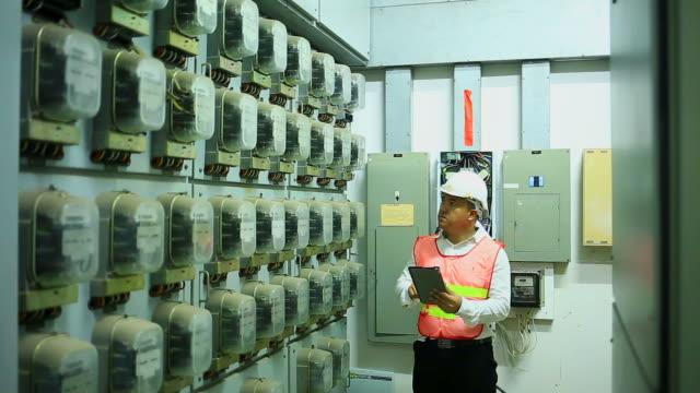 tecnico in sala di controllo alla centrale solare - componente elettrico video stock e b–roll
