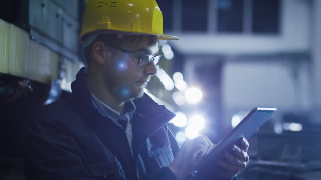 Technician in Glasses and Hard Hat Using Tablet in Industrial Environment video