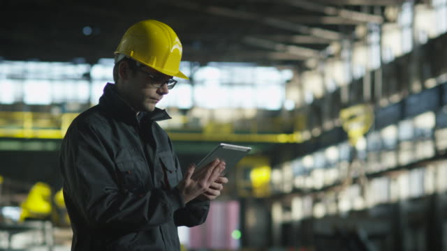 Technician in Hard Hat in Working in Industrial Environment. Holding Tablet in Hands. Technician in Hard Hat in Working in Industrial Environment. Holding Tablet in Hands. Shot on RED Cinema Camera in 4K (UHD). manufacturing occupation stock videos & royalty-free footage