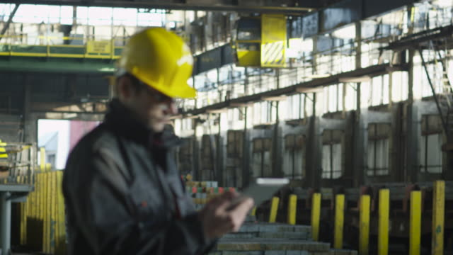 Technician in Hard Hat in Working in Industrial Environment. Holding Tablet in Hands. video