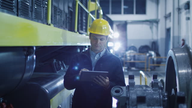 Technician in Hard Hat Using Tablet in Industrial Environment.