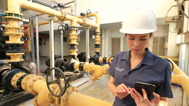 Technician inspects industrial control room video