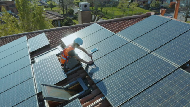 Technician installing and working on maintenance of solar photovoltaic panel installed on domestic home rooftop Aerial shot of technician with hard hat and safety equipment installing and working on maintenance of photovoltaic panel system installed on home domestic roof top, urban landscape. Wide angle camera. work helmet stock videos & royalty-free footage