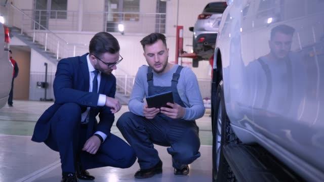 techniker männlich mit tablet kommuniziert mit dem verbraucher in der nähe von auto-rad in der auto-werkstatt - werkstatt stock-videos und b-roll-filmmaterial