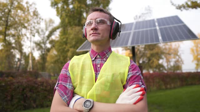 Technician or engineer with protective headphones standing near the solar panel. Man wearing safety equipment hearing protection. Worker wearing noise cancelling ear defenders or ear muffs.