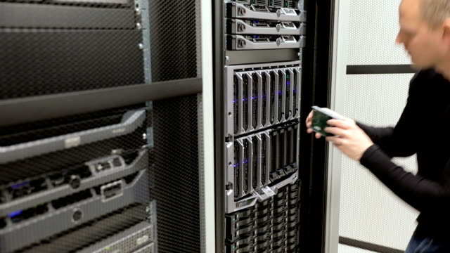 IT technician removes harddrive from blade server in datacenter video