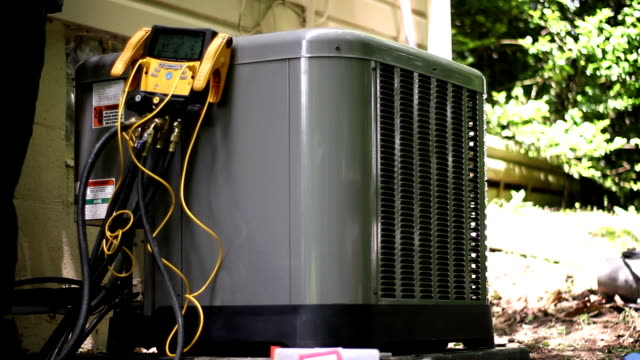 HVAC technician runs refrigerant tests on new operational business grade air con video