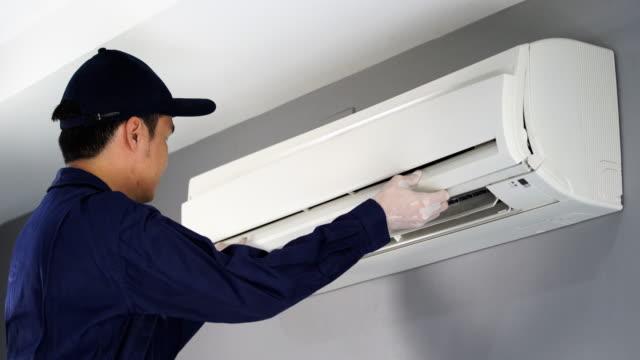 vídeos de stock, filmes e b-roll de técnico de serviço de verificação e reparação de ar condicionado dentro - ar condicionado