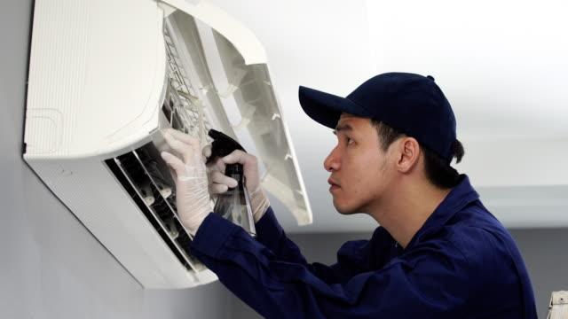 屋内のエアコンを清掃する技術者サービス - エアコン点の映像素材/bロール