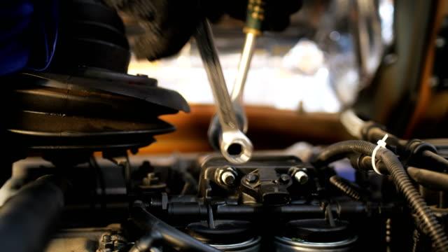 technician twists screws on truck engine at checking closeup - silnik filmów i materiałów b-roll