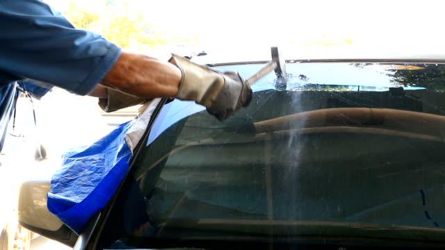 Technician use hammer for Broken car windshield. Selective focus video