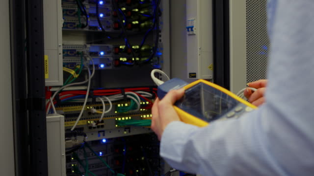 Technician using digital cable analyzer on server video