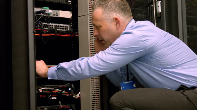 Technician using laptop to analyse server video