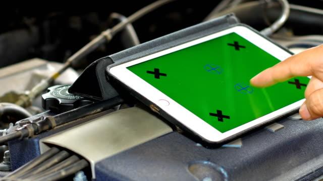緑色の画面でタブレットを使用して診断車、車メンテナンスの概念のための技術者 - 機械工点の映像素材/bロール