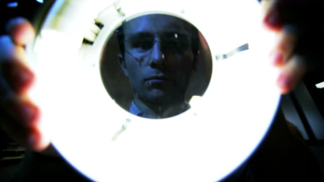 Technician utilize a magnifier lamp in the dark room video