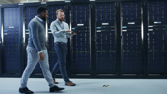 stockvideo's en b-roll-footage met it-technicus met een laptop computer en zwarte mannelijke ingenieur collega zijn talking in data center terwijl naast wandelen server racks. diagnostiek uitvoeren of onderhoudswerkzaamheden te doen. - datacenter