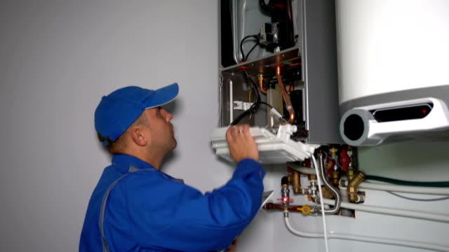 vidéos et rushes de technicien avec le système de chaudière de gaz réglé d'ordinateur et montrent des pouces vers le haut souriant - inspecteur