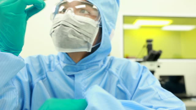 Technician with microchip in the lab clean room video