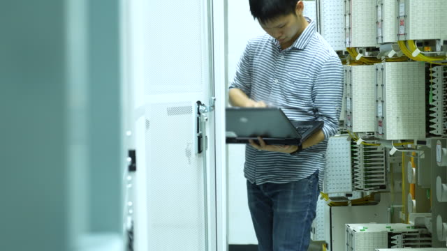 Technician working on laptop in the Wired Network room video