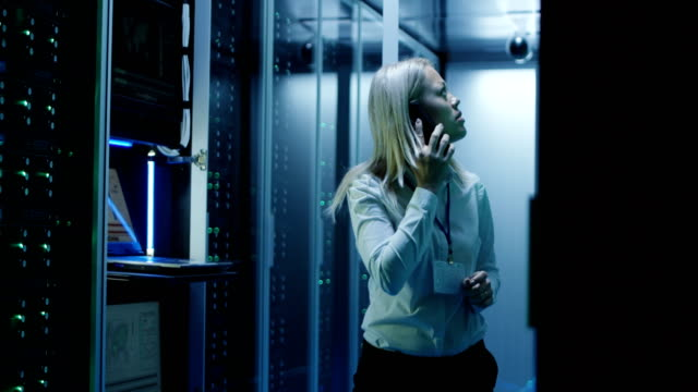 Technician works on a laptop in a data center Medium shot of a female technician working on a laptop in a data center full of rack servers running diagnostics and talking on the phone to a colleague mainframe stock videos & royalty-free footage
