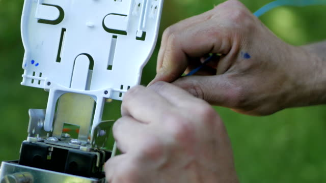 Technicians are installing optic fiber with cable ties. video