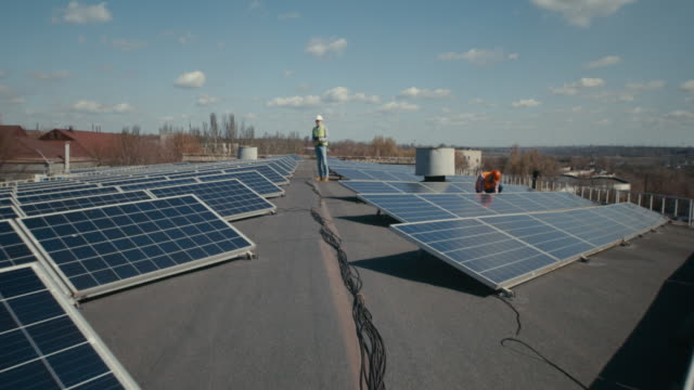 Technicians installing solar panels on flat roof video