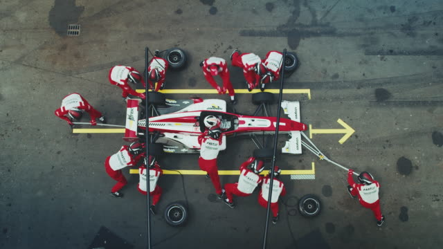 technicians repairing formula one car at pit stop - mechanik filmów i materiałów b-roll