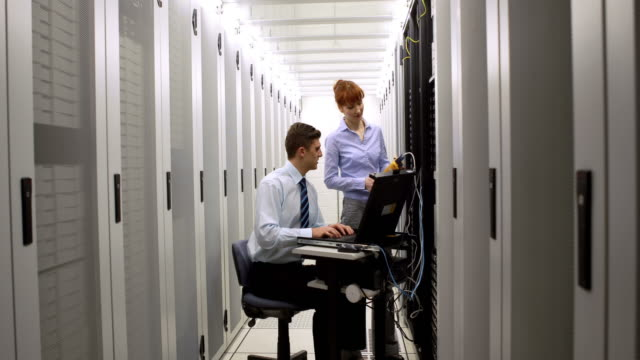 Technicians using digital cable analyzer on server video