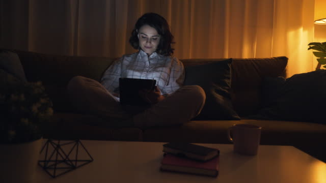 Technology addiction. Cheerful young woman using a digital tablet late in night. She is surfing the net or using social media applications. low lighting stock videos & royalty-free footage