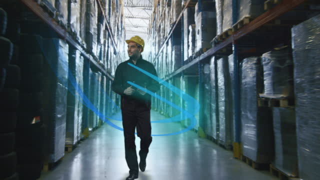 Technology and Networks Concept. Man Walking through Cargo Warehouse. video