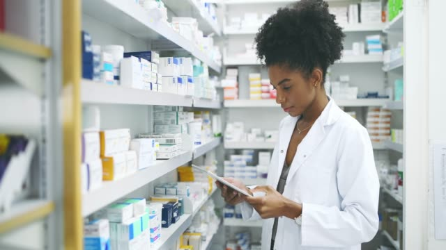Technology changed the way we recommend medicine 4k video footage of a young female pharmacist using her tablet while working in an apothecary pharmacist stock videos & royalty-free footage
