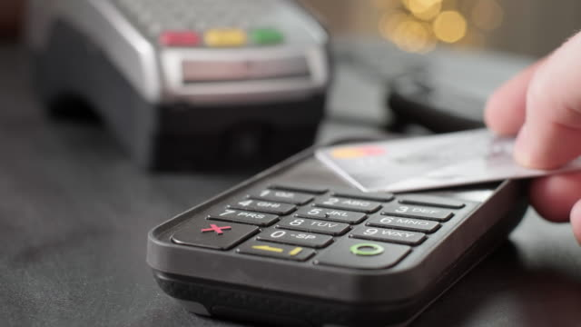 vídeos de stock e filmes b-roll de nfc technology. close-up of young woman using credit card with nfc chip on bank terminal. customer paying for food order outdoor. detail of a client hands paying with the contactless credit card. - paying with card contactless