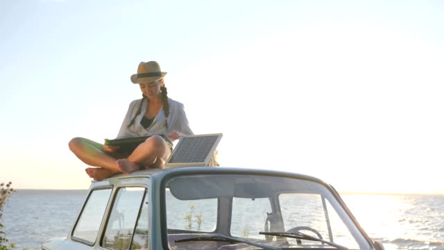technology, girl in vacation sits on roof blue car with solar array charges laptop in backlight, female sitting on vintage car video