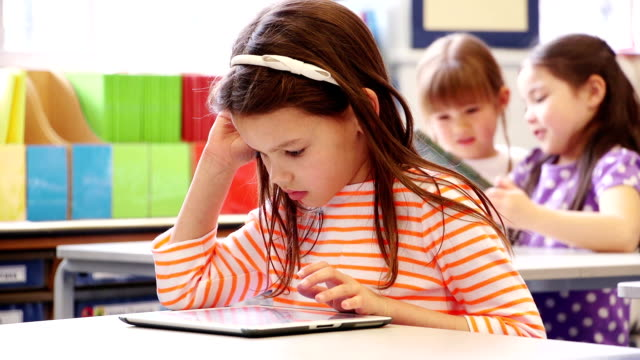 Technology in Class A little girl sitting at her desk using a digital tablet. Two little schoolgirls sat behind her in the background. elementary age stock videos & royalty-free footage