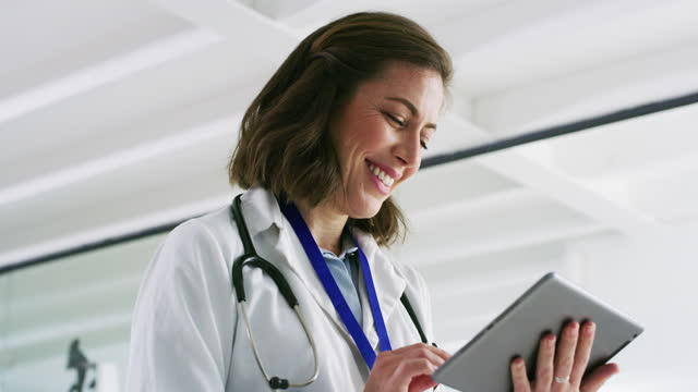 Technology is vital in advancing through the medical field 4k video footage of a doctor using a digital tablet at work general practitioner stock videos & royalty-free footage