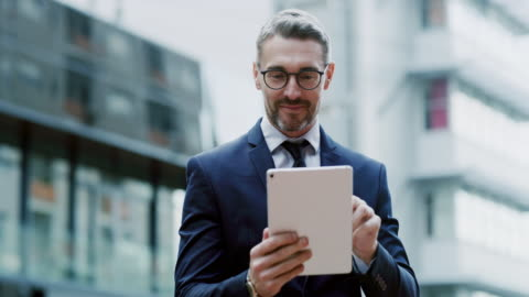 Technology lets me work from anywhere 4k video footage of a handsome young businessman standing outside alone and using a tablet digital tablet stock videos & royalty-free footage