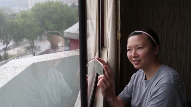 Technology A female adult is using smartphone for taking photo near to bedroom window. one mid adult woman only stock videos & royalty-free footage