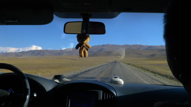CLOSE UP: Teddy bear hangs from a mirror of a car as tourists explore Tibet.