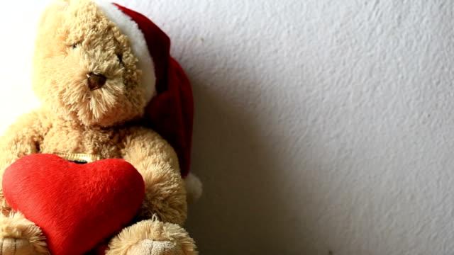 vídeos de stock e filmes b-roll de teddy bear holding head in red on a gray wall background. - teddy bear