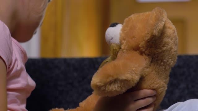 vídeos de stock e filmes b-roll de teddy bear in girls hands - teddy bear