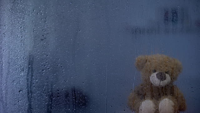 Teddy bear on sill behind rainy window in orphanage, hope and support symbol