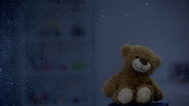 gök gürültüsü hava, umut ve destek yağmurlu pencerenin arkasında eşik üzerinde teddy ayı - kabarık stok videoları ve detay görüntü çekimi