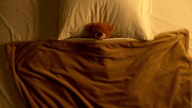 vídeos de stock e filmes b-roll de teddy bear toy lying in bed covered with blanket, childhood memories, innocence - teddy bear