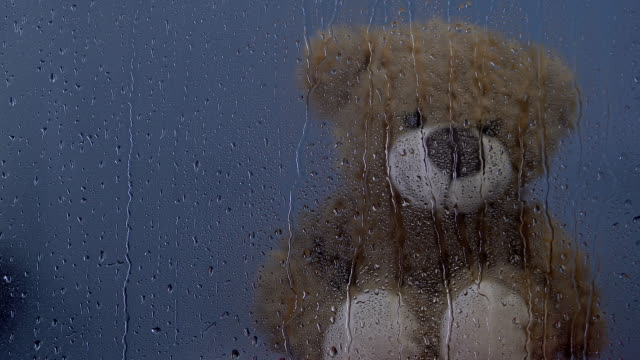 Teddy bear toy sitting behind rainy window in orphanage, water drops dripping