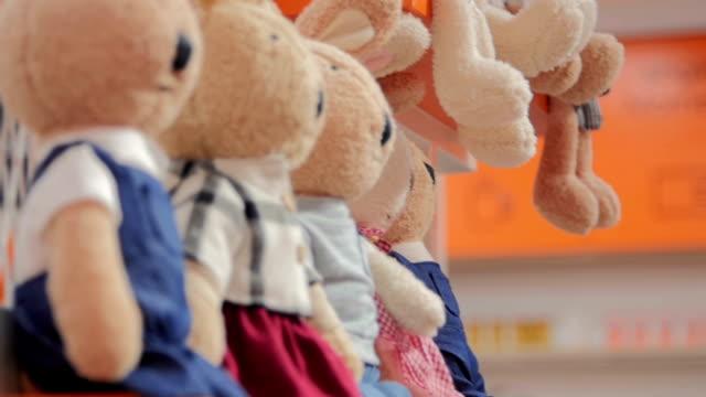 Teddy bears hanged on a shopping mall shelf.