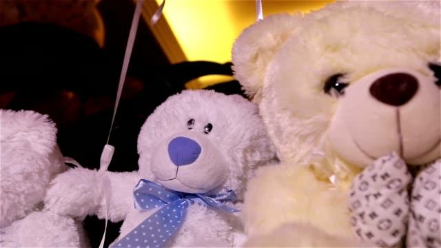 vídeos de stock e filmes b-roll de teddy bears sitting in a row, white teddy bears, helium balloons, cute teddy bear with a butterfly on her neck, soft toy, interior halls for children's birthday, a gift, a room, indoors, teddy bear - teddy bear