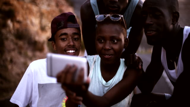 Teen African American girl taking selfie of herself and friends Smiling teenage African American girl taking a selfie of her friends and herself group of objects stock videos & royalty-free footage